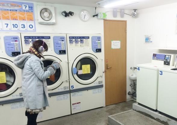 写真中央がバックヤードへの入口、その手前の洗濯機から水漏れしている=2015年2月、撮影・橋本正人