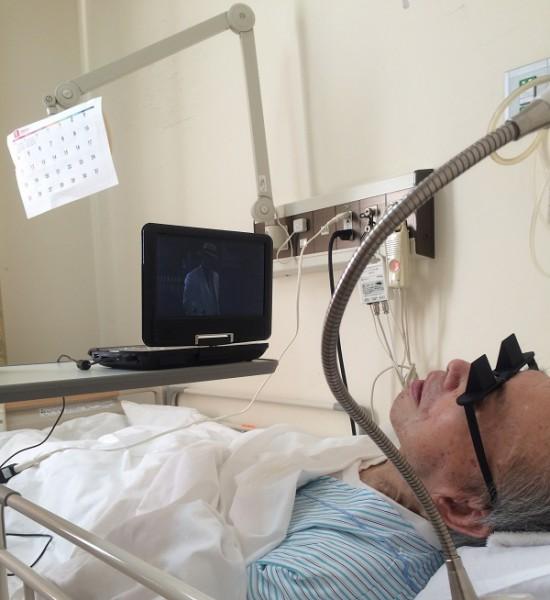 入院先でプリズムメガネをつけて映画を見る父。奥に見えているのはアーム式の電灯にカレンダーを貼り付けたもの。入院していると退院の日が待ち遠しくて、カレンダーを見たくなるんですよね=撮影・橋本正人