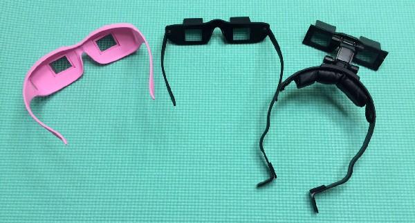 父愛用のプリズムメガネ(中央)と、目にくっつかないタイプ(左)、メガネの上にかけられるタイプ(右)=撮影・橋本正人