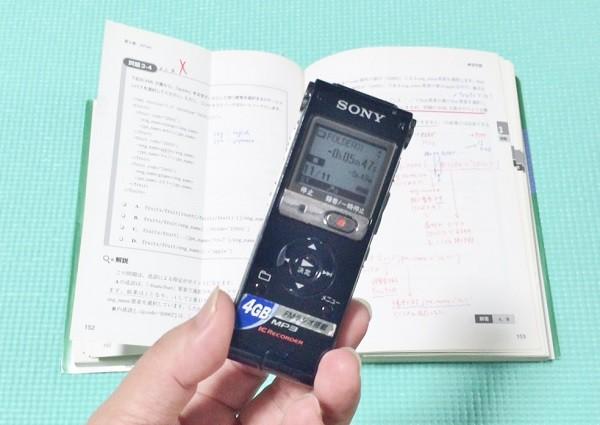 私が愛用しているmp3レコーダ、後ろにあるのは数年前に勉強したXMLの教科書=撮影・橋本正人