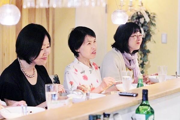 料理を食べながらレシピなどの説明を聞く料理教室参加者ら=撮影・橋本正人