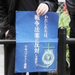 安保法案反対のデモ行進が進む沿道で「わたしたちは、戦争法案に反対します。」と書かれた日本バプテスト連盟のポスターを掲げる人=2015年9月13日、大阪市内で、撮影・橋本正人