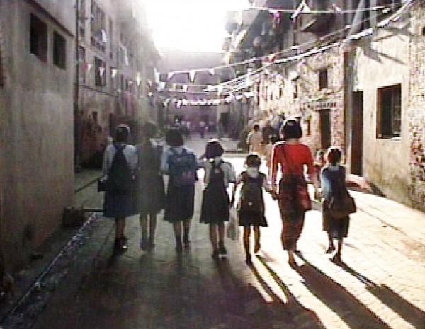 教え子たちとネパール・パタン市の町を歩く佐野由美さん=映画『with…若き女性美術作家の生涯』より