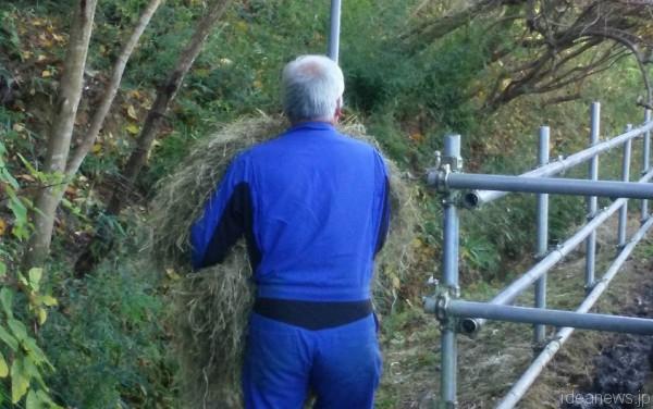 牧場の柵の外を、わら餌を抱えて歩く直登さん=撮影・松中みどり