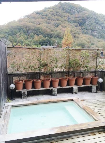 露天の貸し切り温泉(家族風呂)。植木の向こう側は武庫川で、その奥に見えているのは川向うの宝塚市側の山です=2015年11月13日、撮影・橋本正人