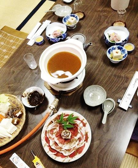 昼食として食べた「名物ぼたん鍋コース」。猪の肉を特製の味噌を溶かしたスープで煮込みます。上の方の皿に乗っているのは、鯉のあらい(刺身)と、ごま豆腐=2015年11月13日、撮影・橋本正人