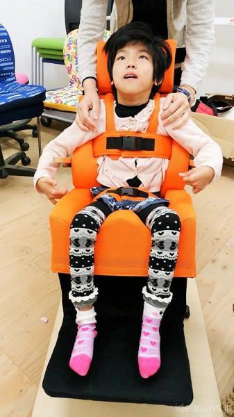 完成した補装具がセットされた椅子に座るレノアちゃん=撮影・松中みどり