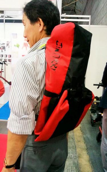 「JINRIKI®QUICK」のパイプを専用バッグに入れて背負っている中村社長 2016年4月22日「バリアフリー展」にて=撮影・松中みどり