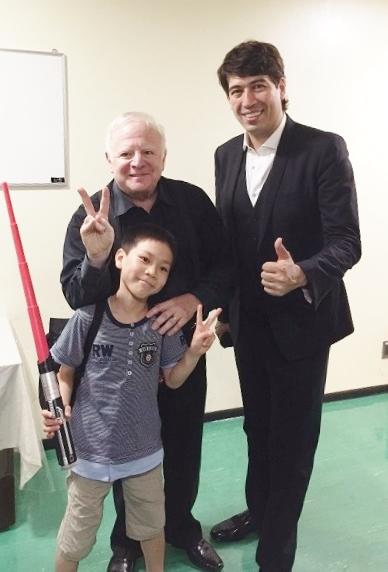スターウォーズの「ライトセイバー」を持ってNHKホールで指揮をした子どもとレナード・スラットキンさんとMCを務めたサッシャさん=写真提供・KAJIMOTO