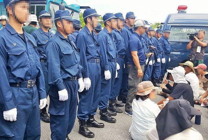 ヘリパッド工事を止めたいと座り込む沖縄の人々と、機動隊員=写真提供・川口真由美さん