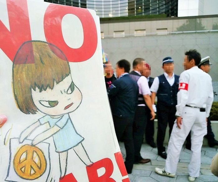 「NO WAR」の手製プラカードを掲げて抗議=2016年7月19日大阪府警本部前で、撮影・松中みどり