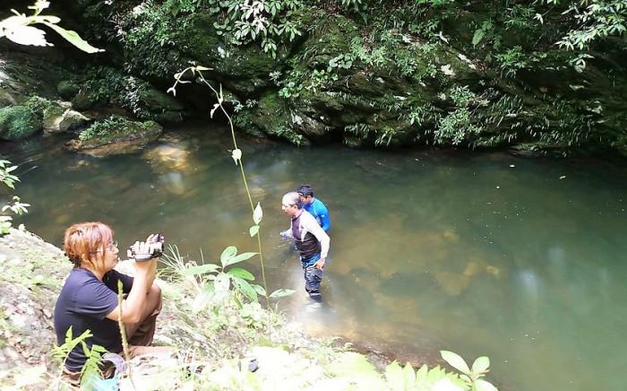 滝の近くでお昼ご飯 はしゃぐ参加者を撮影中のアキノ隊員 =撮影・松中みどり