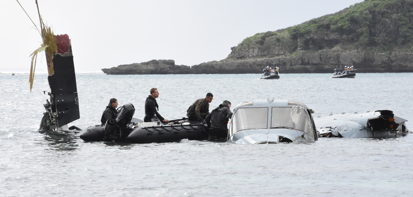 墜落したオスプレイのコックピットを捜索する米兵。海上保安庁のゴムボートが遠巻きに見守る=2016年12月14日、名護市安部、撮影・阿部岳