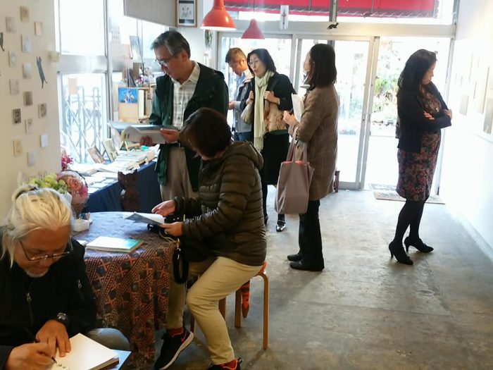「やさしいねこ」写真展最終日の様子。左下は本にサインする著者・太田康介さん=撮影・松中みどり