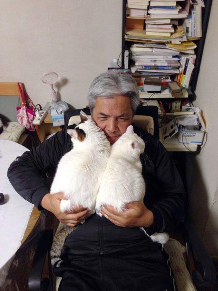 太田家の先住猫「しろ」(右)と一緒に、太田さんのひざに乗れるまでになった「ぽー」=写真エッセイ『やさしいねこ うちの ぽー』より