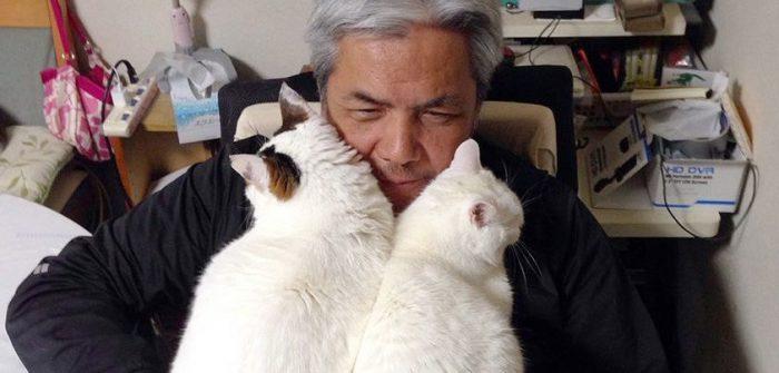 太田家の先住猫「しろ」(右)と一緒に、太田さんのひざに乗れるまでになった「ぽー」=写真集『やさしいねこ うちの ぽー』より