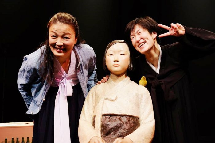 4月22日・23日の舞台『キャラメル』少女像を真ん中にポーズをとる洪美玉さん(左)ときむきがんさん(右)=きむきがんさんのFacebookページより