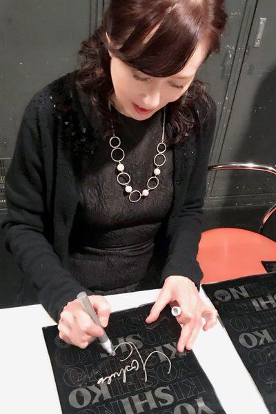 アイデアニュース読者プレゼントのビニールバッグにサインする木住野佳子さん=撮影・堀内優美