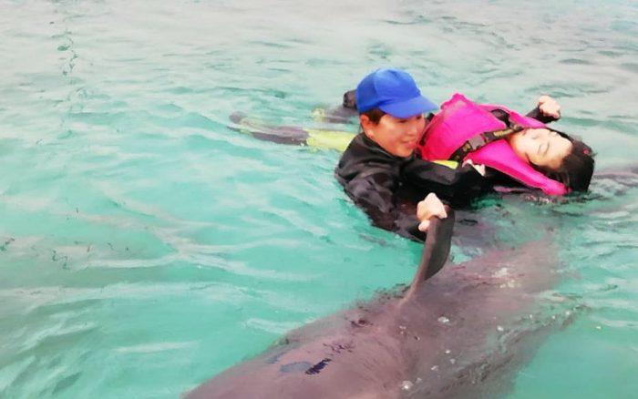 「ドルフィンリゾート」のスタッフと一緒にイルカと泳ぐレノアちゃん=撮影・松中みどり