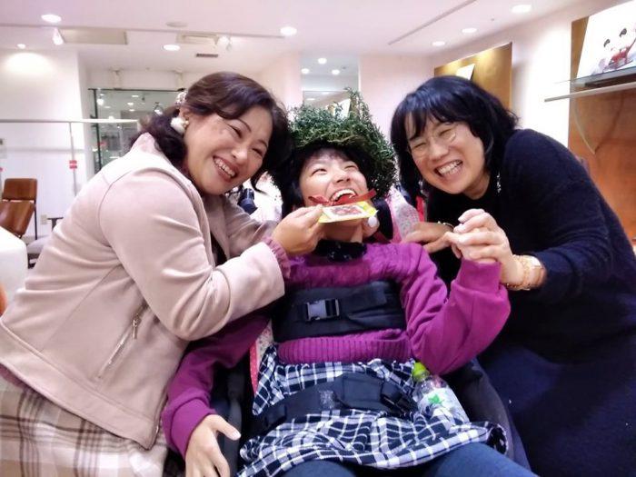 一足早くハーブの冠を被り、クッキーのメダルをかけたレノアちゃん 右はPASの野村寿子さん 左はお母さんの敦子さん=撮影・松中みどり