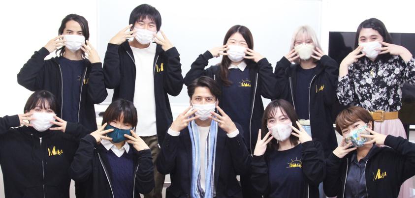 両手の3本指を顔の横につける「みーあキャットのポーズ」をとる、伊礼彼方さんと大阪大学ミュージカルサークル「みーあキャット」のみなさん=撮影・橋本正人